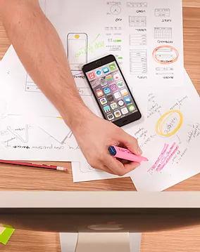 Bureau avec feuilles et smartphone pour illustrer le sourcing